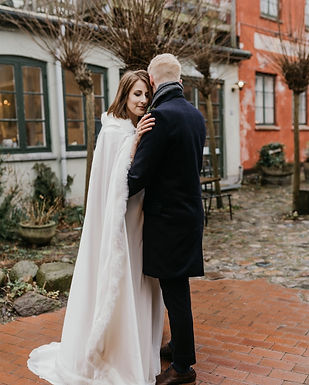 A groom and bride embracing during their romantic adventure abroad, enjoying the Danish bridal islands for their intimate wedding.