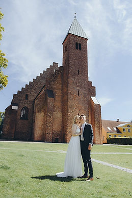 Alicia and Reno standing in from of the Great Cathedral during their Nordic Adventure Wedding.