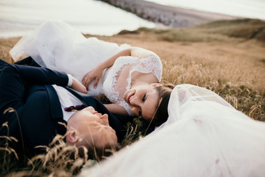 Newlyweds relaxing in a field by the beach during their island wedding adventure in Denmark after booking our elopement wedding package abroad for two.