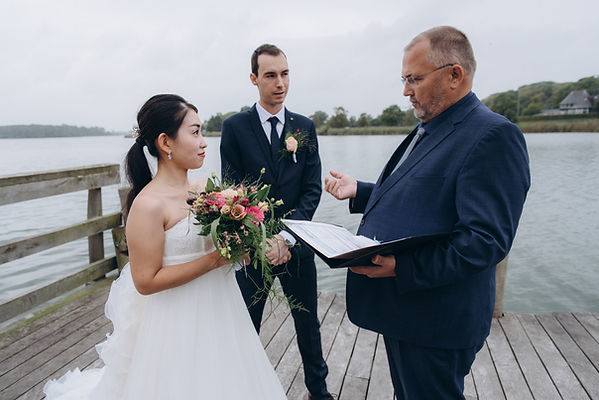 A couple eloping to Denmark, pictured by the Maribo lake for their outdoor island wedding in Denmark instead of a Denmark city hall wedding.