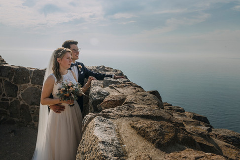 A couple hugging at the top of the Hammershus Ruins in Bornholm Island and looking outwards at the Baltic Sea, enjoying their experience of getting married overseas.