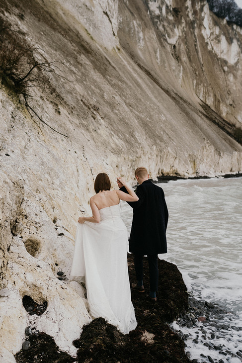 Newlyweds holding hands and exploring Mons Klint during their winter elopement in Denmark