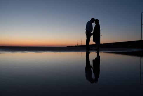 A silhouette sunset portrait photograph of a couple that had their vows renewal abroad