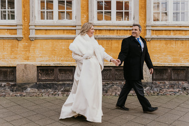 Husband and wife walking through Maribo town in Lolland Island during their picturesque Nordic winter wedding in Denmark