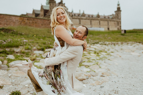 A husband lifting up his wife off the ground during their intimate wedding abroad in Denmark, pictured here in front of Hamlet's Elsinore Castle
