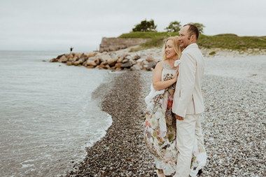 Husband and wife looking out into the horizon as they enjoy their island wedding adventure in Denmark, a perfect destination for elopements and small intimate weddings abroad.