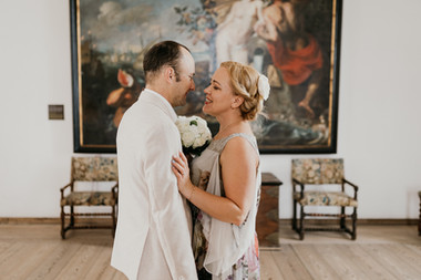 A wife smiling at her husband as they renew vows abroad in Hamlet's Castle in Denmark, also perfect for destination weddings.