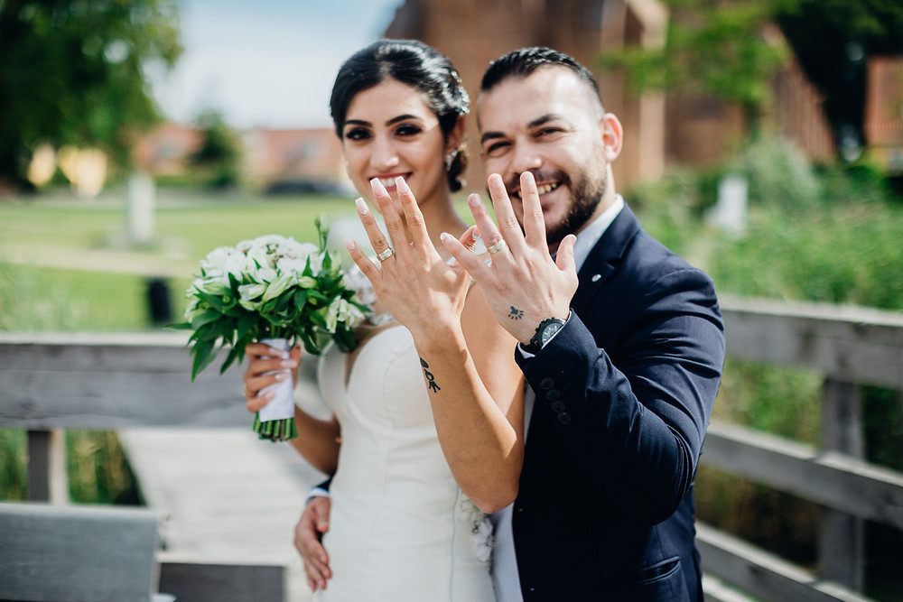 Elias & Mary showing their happy smiles and wedding rings after their quick marriage in Denmark.