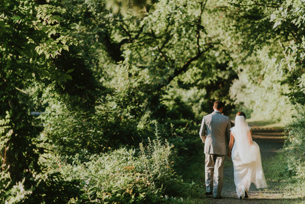 Newlyweds walking through the forest during their elopement to Møn Island after booking our wedding package abroad for two for their small intimate wedding abroad.
