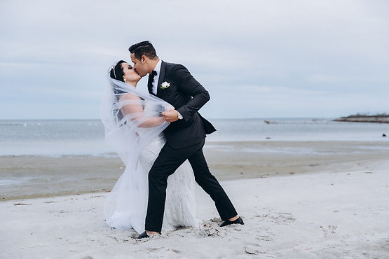 Rita and Benny kissing at Bandholm beach during their adventure wedding experience.