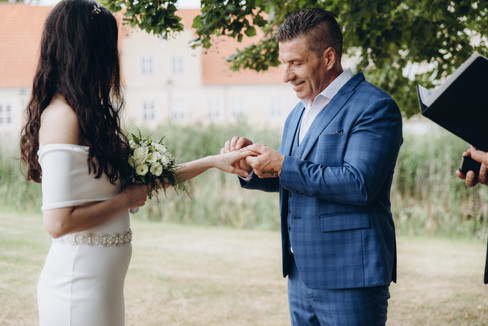 A husband placing a ring on his wife's finger during their intimate wedding in Denmark.
