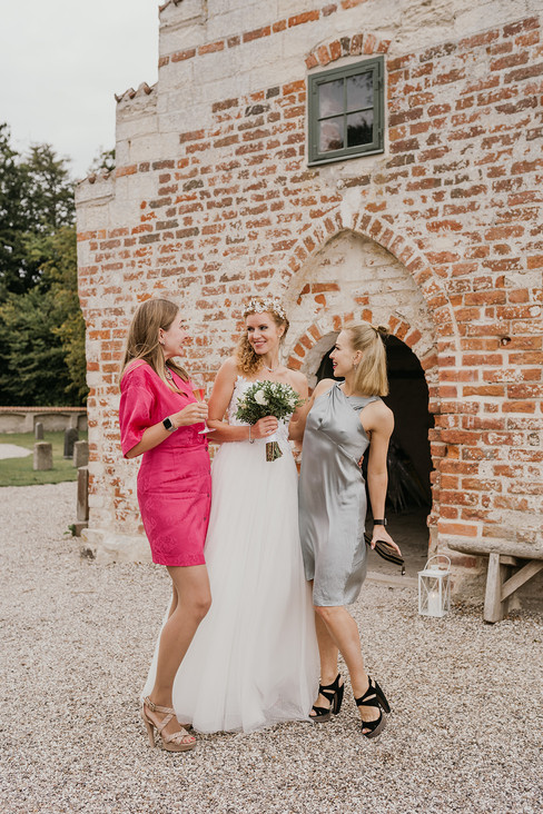 A bride with her bridesmaids in front of the ancient historical church during a small wedding abroad in Denmark.