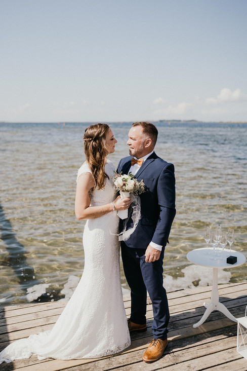 Husband and wife smiling and looking into each other's eyes as they enjoy their beach wedding in Denmark, one of the best places to get married abroad