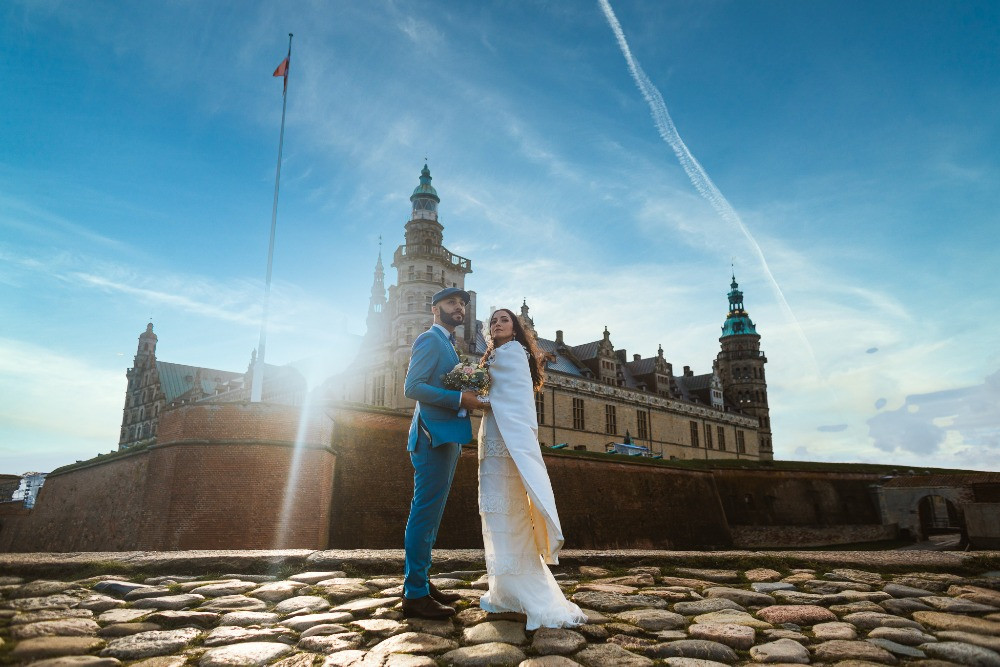 Couple posing in the front of Kronborg castle during their elopement abroad in Denmark
