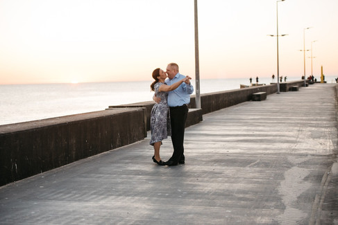 A married couple laughing and holding hands at the pier, a simple but intimate way to renew your vows abroad