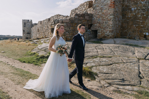 Newlyweds walking through the Hammershus Ruins and holding hands as they enjoy their Bornholm Island wedding adventure in Denmark, one of the best places to get married abroad