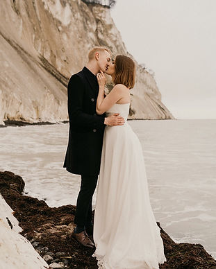 A couple kissing in front of Mons Klint during their Denmark wedding adventure.