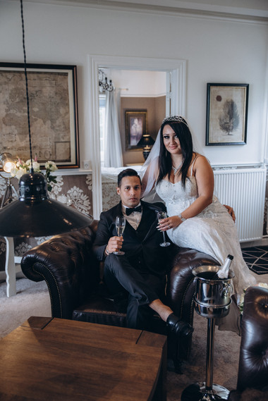 A lovely wedding portrait of husband and wife as they sit inside a lounge area in a Maribo hotel in Lolland Island, one of the best places to elope abroad, booked with one of our Denmark elopement packages.