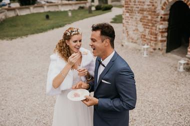 A bride feeding her husband their celebration cake during their intimate wedding abroad during their Danish wedding.