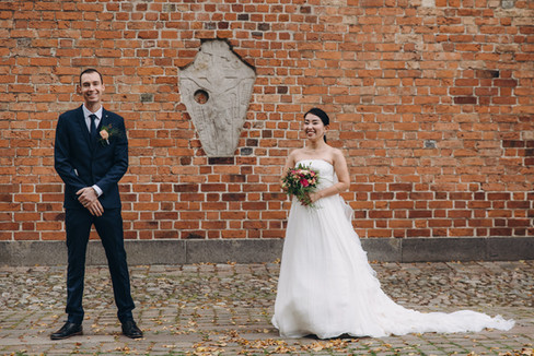 A portrait of husband and wife in the front of Maribo cathedral, one of the best places to elope abroad.