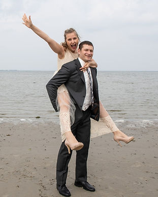 A husband giving his wife a piggyback ride during their wedding in Denmark.