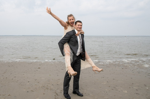 A groom giving his happy bride a piggyback ride as they enjoy their Scandinavian wedding by the beach in Denmark during their adventure on Lolland Island.