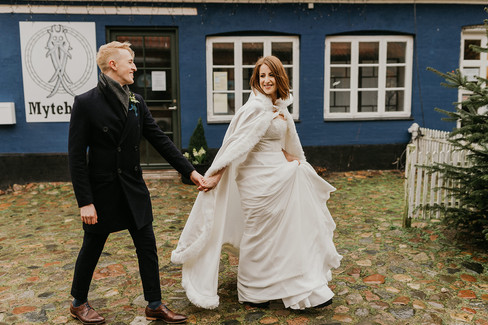 Husband and wife holding hands as they roam the streets of Mon Island during their dream winter wedding adventure in Denmark