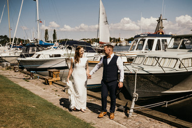 Newlyweds holding hands as they enjoy Lolland Island's marina, a great marry abroad idea for an overseas wedding.