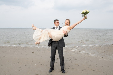 A groom lifting up his joyous bride as they have fun during their beach wedding in Denmark on Lolland Island