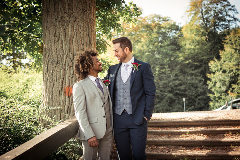 A gay couple smiling in the woods during their same-sex wedding in Denmark