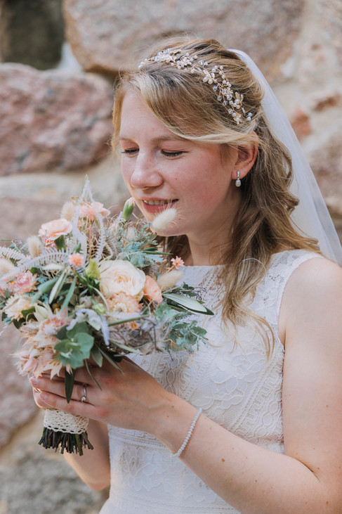 A bride smelling her bouquet of wildflowers while getting married in Denmark on Bornholm Island as a part of our wedding packages abroad for two.