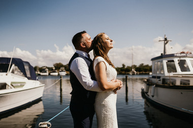 Newlyweds embracing at the marina in Lolland island on a sunny day, enjoying their beach wedding in Denmark