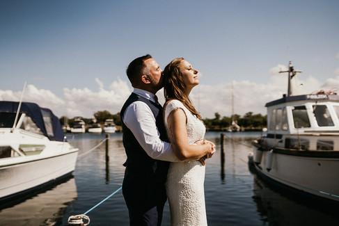 Newlyweds embracing at the marina in Lolland island on a sunny day, enjoying their beach wedding in Denmark