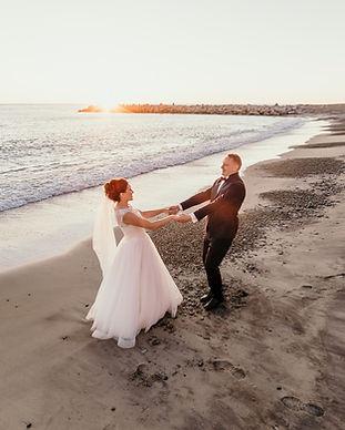 Newlyweds dancing during their beach wedding in Denmark in Lolland Island.