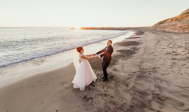 Newlyweds dancing by the shore during their dream beach wedding overseas in Denmark made possible by our amazing packages abroad for two.