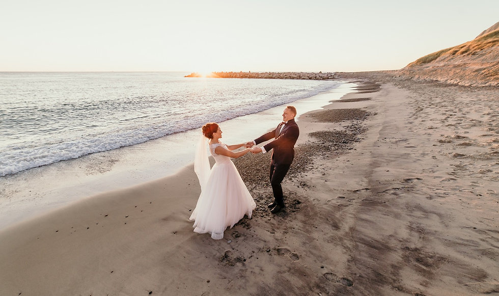 A couple dancing on a calm Nordic beach during sunset, almost like they have their own island for their wedding.
