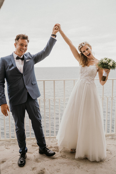 Newlyweds holding their hands up in celebration and laughing during their adventure elopement in Denmark.