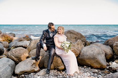 A couple sitting on large rocks by the sea and looking into each other's eyes during their adventure elopement in Denmark.