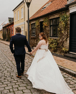 Newlyweds walking through the colorful streets of Maribo town in Lolland Island as they get married in Denmark during their adventure elopement abroad.