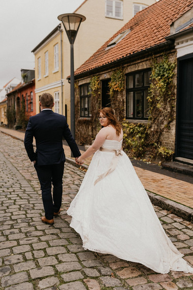 A bride looking back at the camera as she holds hands with her husband, exploring the picturesque Maribo town during their marriage in Denmark.