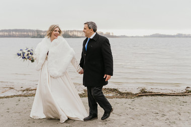 Husband and wife holding hands and walking by the water during their winter elopement to Denmark