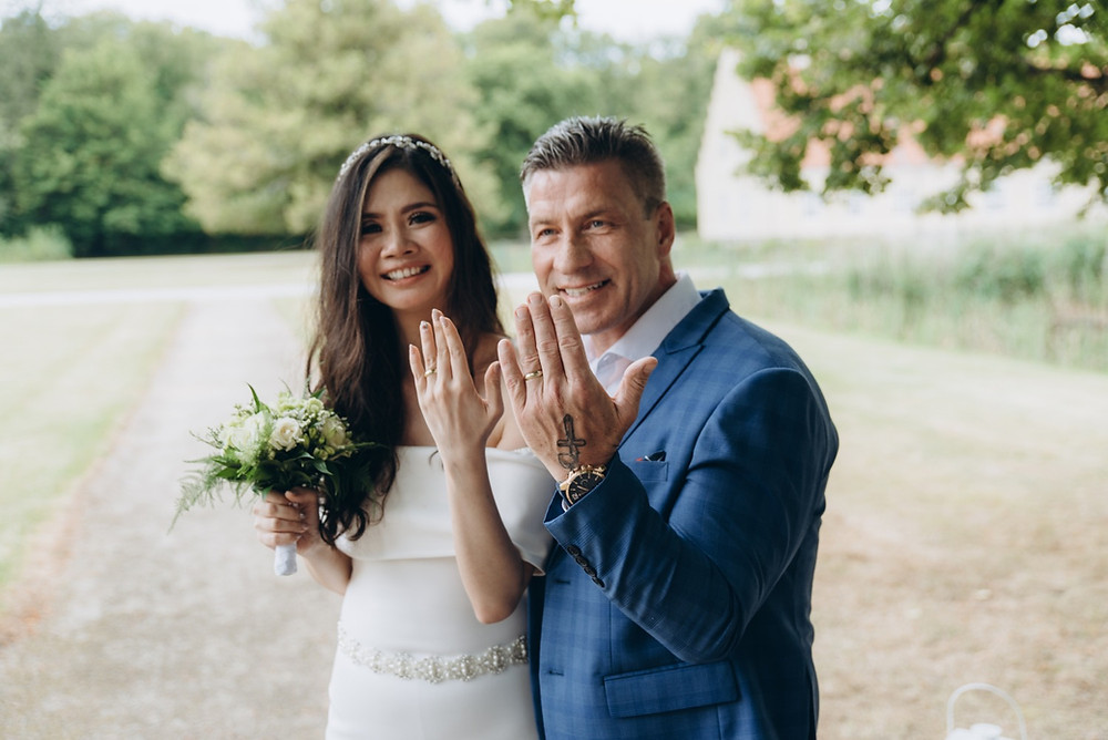 A newlywed showing their rings after getting married abroad in Denmark.