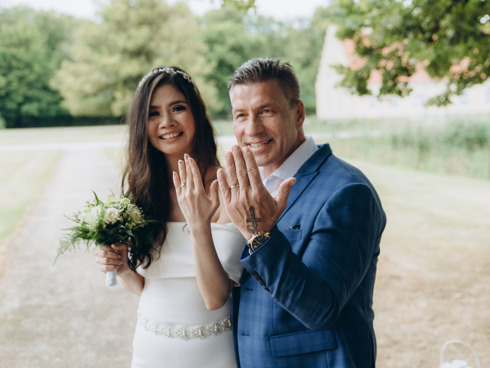 a couple showing their wedding rings and smiling at the camera during ther marriage in Denmark for foreigners experience.