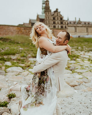 A husband lifting up his wife with Hamlet's Elsinore castle in the background, making their vows renewal idea finally come true
