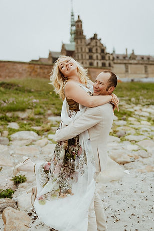 A groom hugging and lifting his bride off the ground in happiness, pictured in front of Hamlet's Elsinore Castle, one of the best locations for small destination weddings, made possible by Nordic Adventure Weddings, your wedding abroad planners.