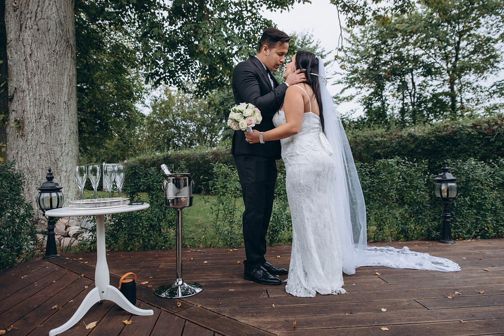 A groom looking at the crying bride while their small wedding abroad in Denmark