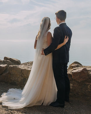Newlyweds looking at the horisont at ancient ruins, the best wedding venue for adventure elopement
