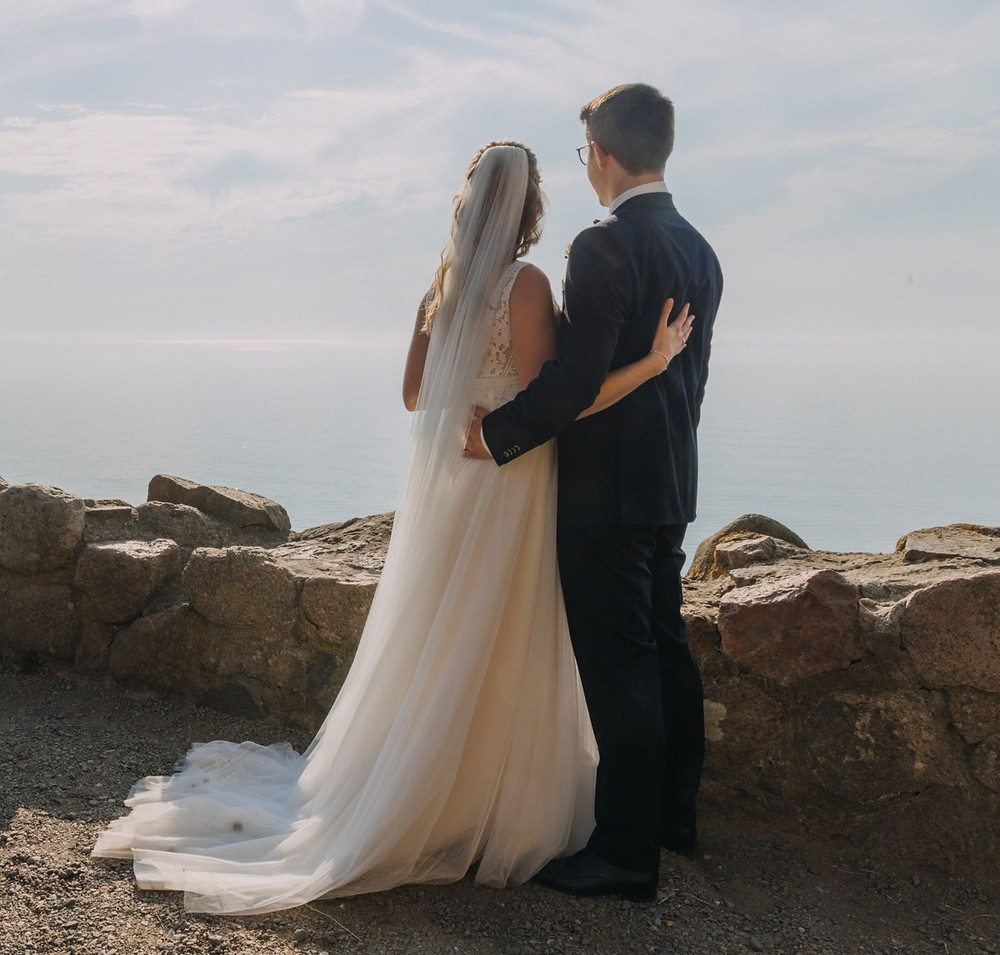 Newlyweds looking to the sea after they get married in Denmark on Bornholm