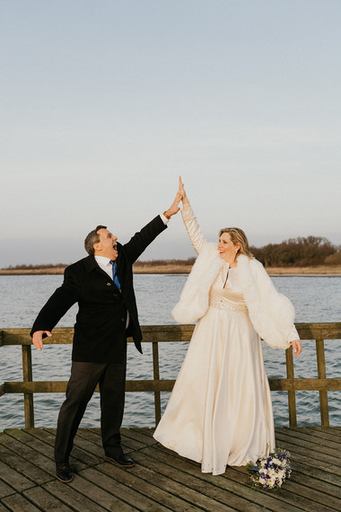Newlyweds giving a thumbs up and smiling during their intimate wedding abroad in Denmark.