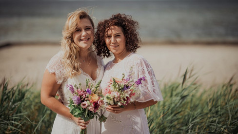 A lesbian couple smiling holding bouquets by the beach during their LGBT wedding in Denmark.